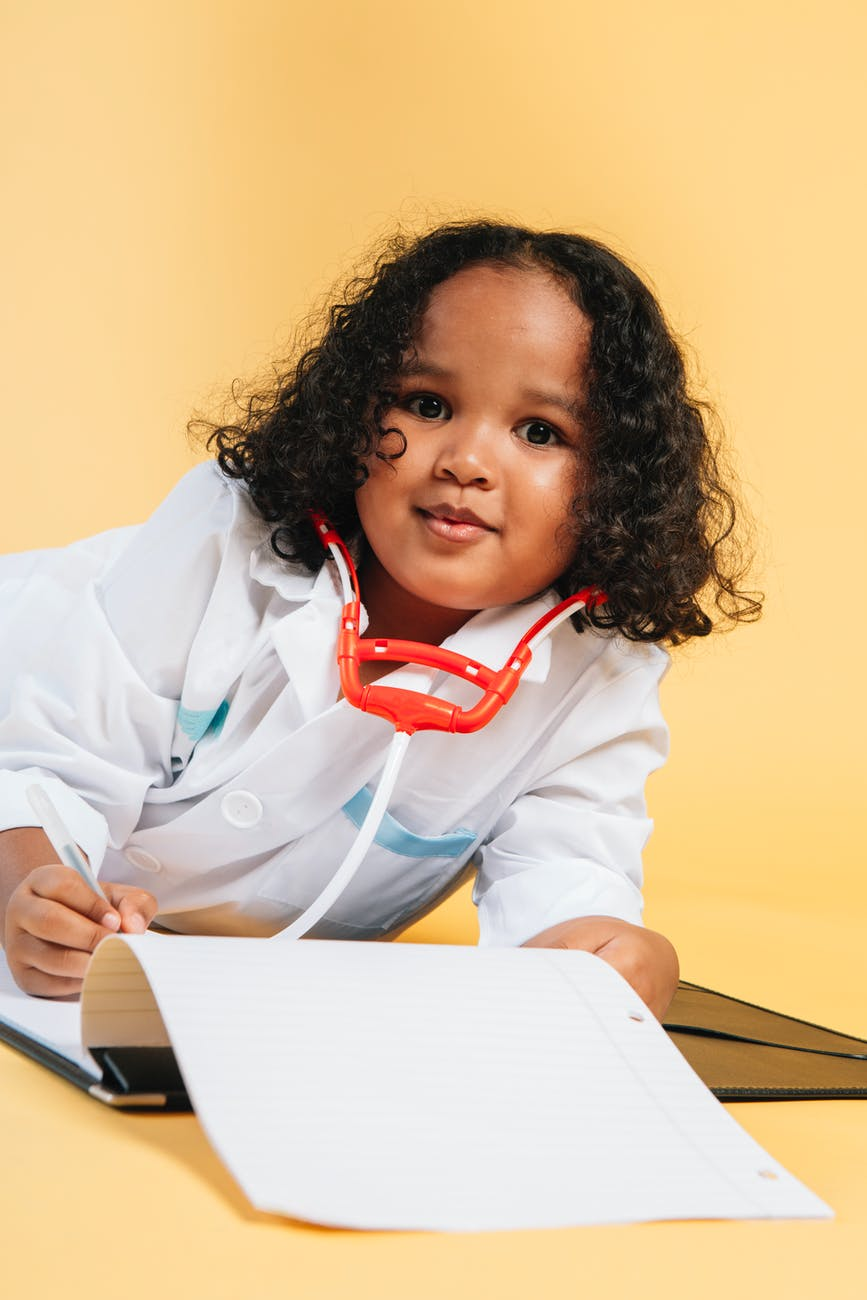 cute black child imitating doctor while playing in studio